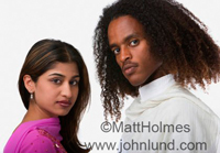Portrait stock photo of a mixed race couple looking back over their shoulders at the camera. She is Indian and He is of African Descent
